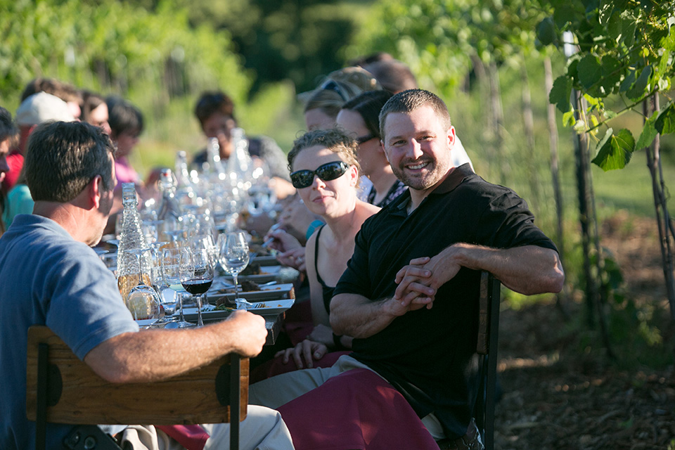 Guests Laughing at Dinner in the Vineyard